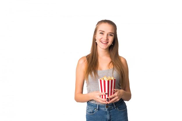 灰色のタンクトップでかわいい女の子はカメラに笑顔し、ポップコーンを手に持っています。