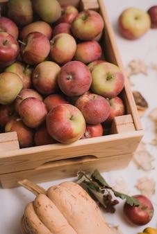 自宅のテーブルに素朴な甘いリンゴの箱。秋の静物。