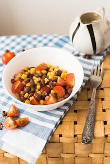 小豆のサラダ、イエローコーン、クラッカー。ピクニックバスケットと美しい青いタオル。