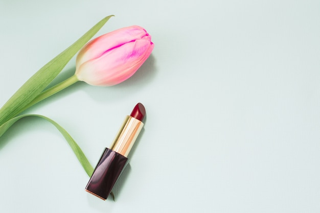 柔らかい青いパステル調の背景に赤い口紅。チューリップの花と口紅。テキストのための場所。国際婦人デー