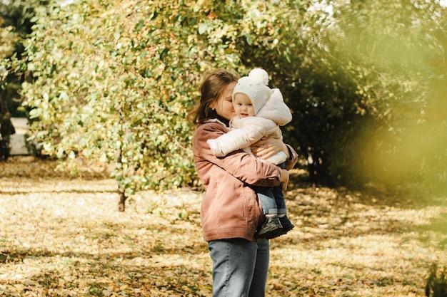 かわいい、若い母親は秋の公園で赤ちゃんを投げます。ママと娘は美しく日当たりの良い森を歩いています