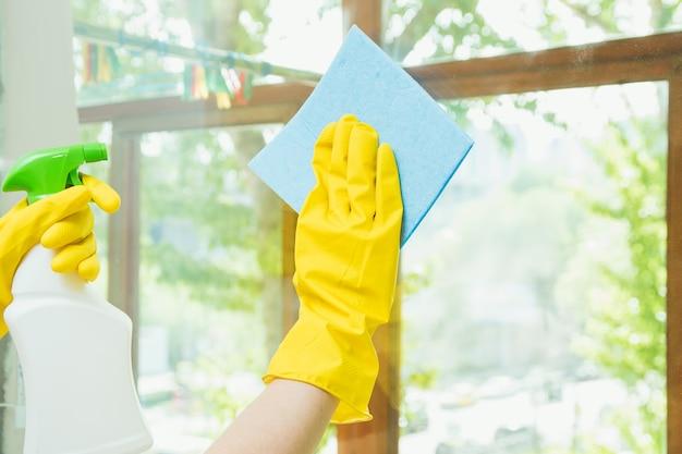 Клининговая компания очищает окно от грязи. домохозяйка полирует окна дома.
