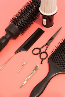ピンクの表面に設定美容院でフラットレイアウト構成。はさみ、櫛、ヘアクリップなどのツールと機器を備えた理容室。美容室および美容室サービス