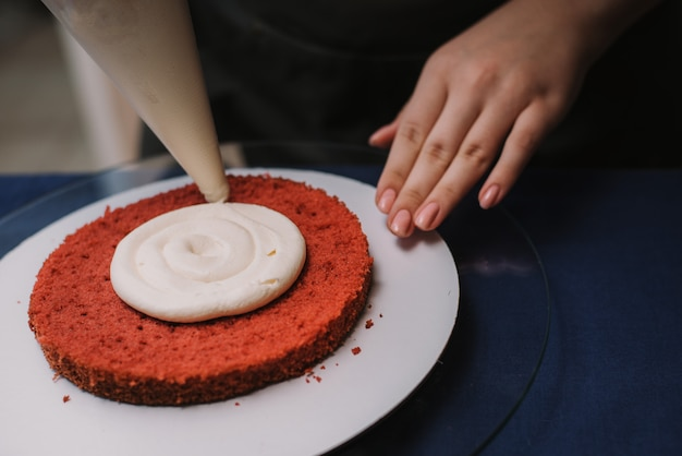 Кондитер сжимает сливки на торте. женщина делает торт