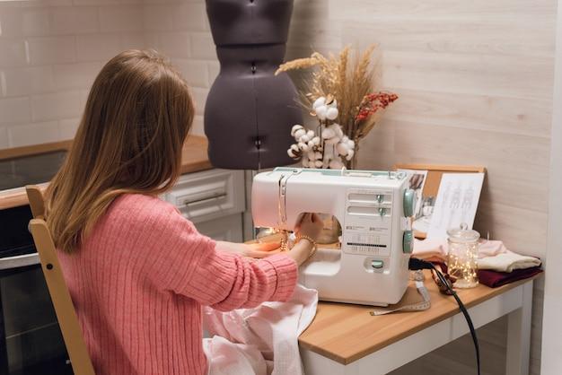 裁縫師はミシンで働いています。女性はピンクの布を縫って保持します