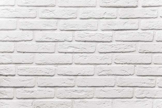 長い白いレンガ壁の背景。白いペンキで描かれた古いレンガのテクスチャ