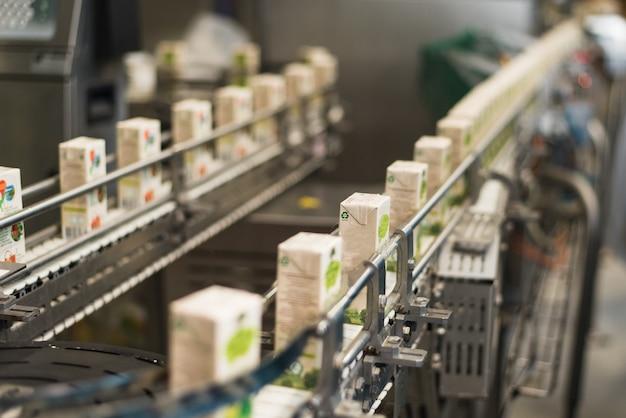段ボール包装のジュースの生産と瓶詰めのための工場のコンベヤ。