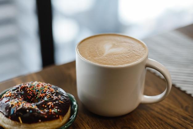 コーヒーショップで木製のテーブルに描かれた心とミルクとコーヒー。コーヒーの隣のテーブルに散らばったピンクのドーナツ