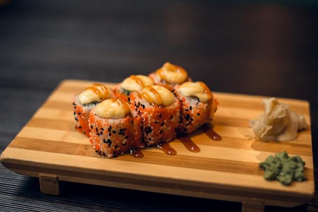 Комплект горячих испеченных булочек на деревянном подносе с имбирем и васаби. вкусные суши в китайском ресторане