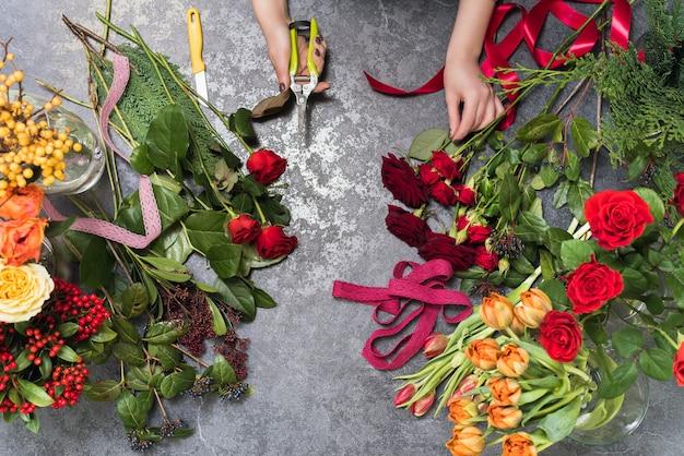 Флорист создает букет в цветочном магазине. вид сверху на создание букета из красных, оранжевых, бордовых, желтых роз, тюльпанов.