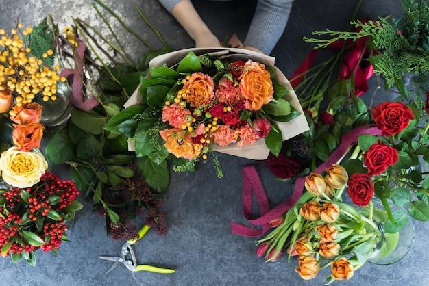 Флорист создает букет в цветочном магазине. взгляд сверху красивого букета красных, оранжевых, бургундских, желтых роз, тюльпанов.