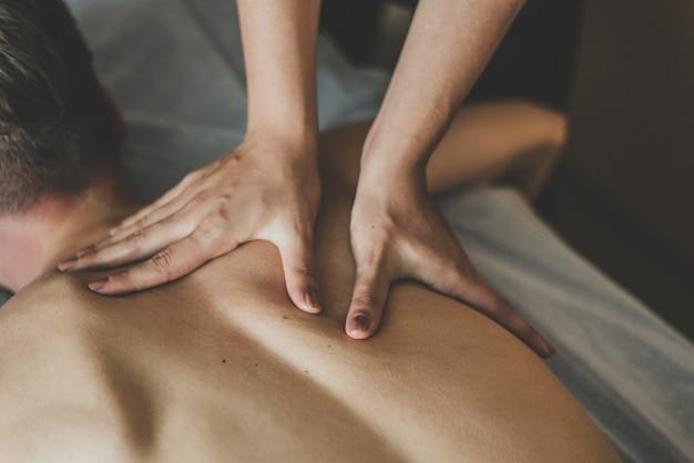 Мужчине делают массаж спины. отдых на массажном столе. красивая тонировка