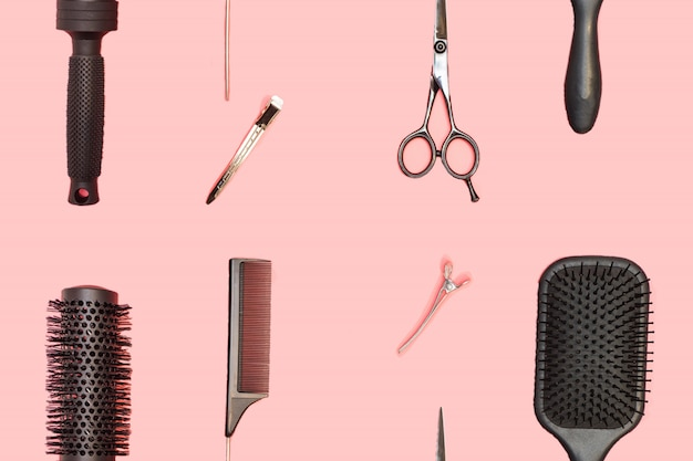 ピンクのテーブルに設定美容院とのシームレスなパターン。はさみ、櫛、ヘアクリップなどのツールと機器を備えた理容室。
