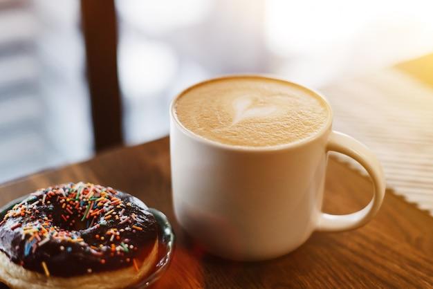 コーヒーショップで木製のテーブルに描かれた心とミルクとコーヒー。コーヒーの隣のテーブルに散らばってチョコレートドーナツ