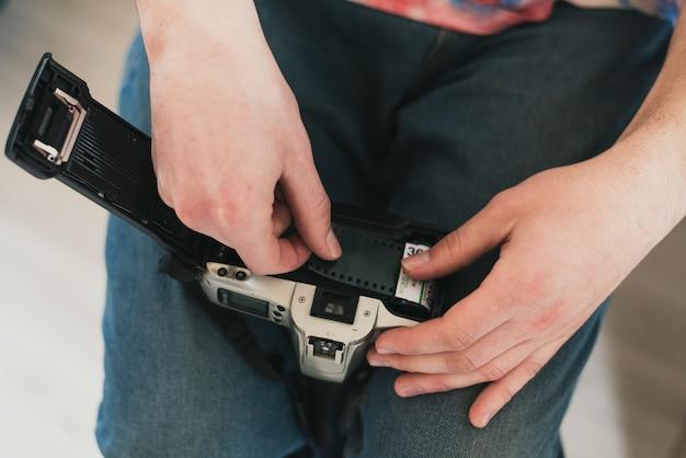 男がカメラのフィルムを埋めます。カメラにフィルムを入れます。テープを機械に入れます。