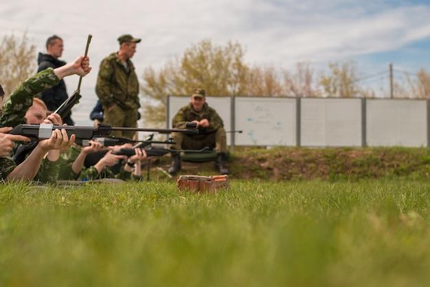 Солдаты лежат на земле и целятся в цель. армейские учения.