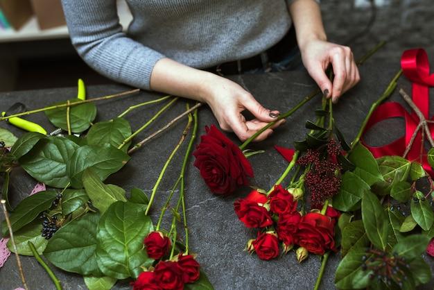 美しい女性は、バーガンディの赤いバラの暗い花束を収集します。フラット横たわっていた、トップビュー。花の配達、注文の作成、中小企業