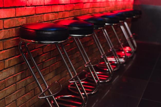 ネオンの光のカウンターでバースツール。ナイトクラブのバーで革張りの椅子