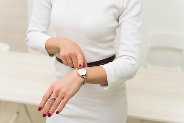 Женщина показывает часы на руке. деловой стиль