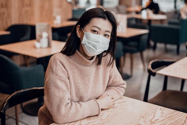 防護マスクのアジアの女性はカフェに座っています。気道を保護することにより、ウイルスから集団を保護します。日常生活におけるコロナウイルスの概念