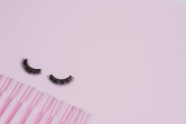 ピンクのトレンディなパステル調の背景に黒の偽リボンまつげとエクステンションまつげをとかすためのブラシ。つけまつげ