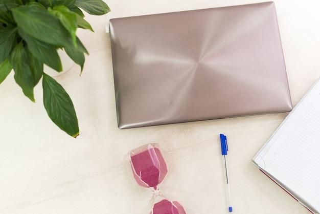 フリーランス。自宅で働きます。職場での時間の分布の概念。時間管理。砂時計、ラップトップ、白いテーブルの上のノート