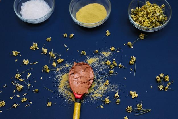Смешанная красная глина с водой в деревянной ложке с сухими цветками ромашки. стеклянные миски с морской солью, сухой глиной и цветами для создания косметики в домашних условиях