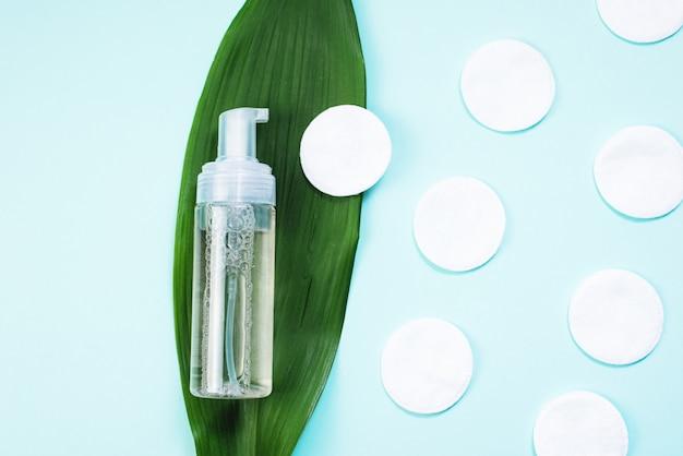 Мицеллярная вода и ватные палочки на пальмовых листьях на пастельно-голубой поверхности. концепция очищения и смывания макияжа. увлажнение кожи с помощью натурального тонера