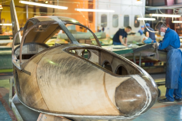 Люди в синих одеждах строят самолет на заводе. рабочие в спецодежде работают над деталями самолета.