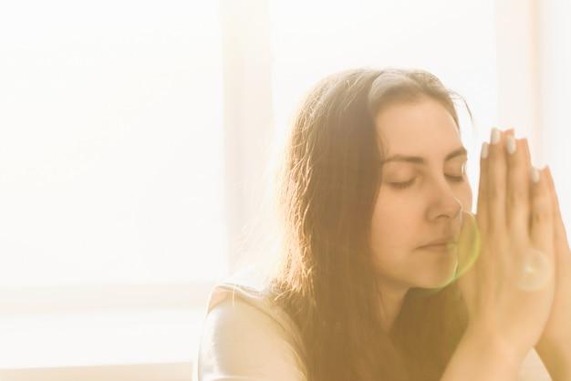 Руки женщины молятся богу. женщина молись о боже, чтобы желающие имели лучшую жизнь. просить прощения и верить в добро. христианская жизнь кризис молитва к богу