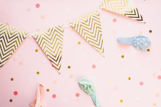Шаблон для праздников. бумажная гирлянда из флагов на розовом фоне с конфетти и воздушными шариками в пастельных тонах. праздничный фон, день рождения