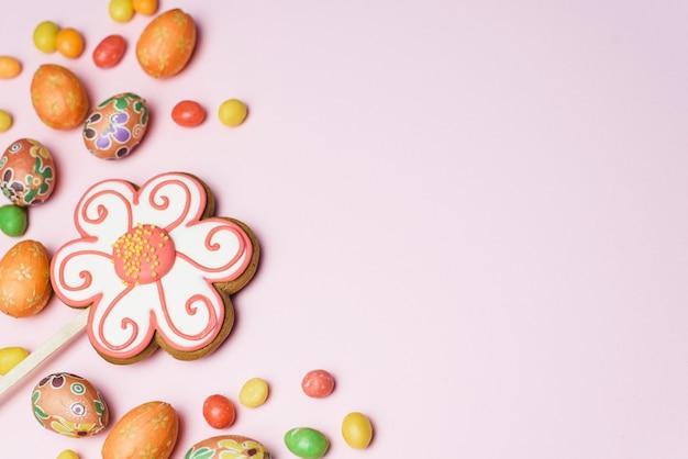Пасхальные пряники, сладкие цветные конфеты и небольшие декоративные яйца на розовом фоне. пасхальная открытка