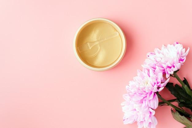 鮮やかな菊の花の横にあるピンクのパステルカラーの壁に金色のパッチ。天然花エキス化粧品、美容、ファッション。ジャー、フラットレイ、トップビューで保湿用のパッチ