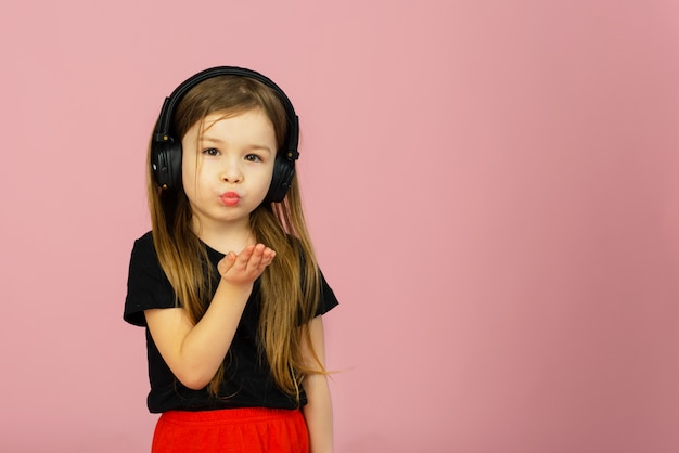 Маленькая девочка слушает музыку в больших наушниках на розовой пастельной стене и целует камеру. искренние эмоции