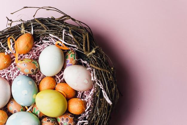 小枝と干し草の巣とパステルカラーのイースターエッグが付いたピンクの紙製フィラー。軽いイースター休暇のための塗装と装飾の卵。ピンクの背景のイースターカード