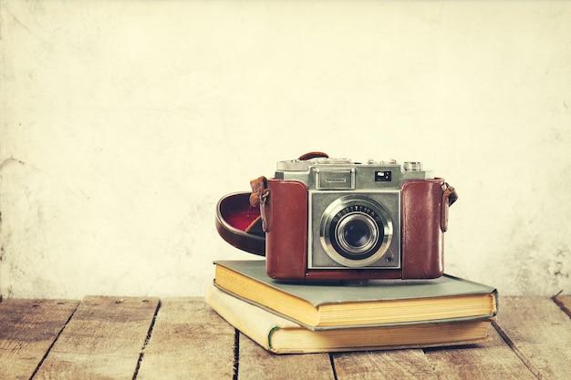 古い木の背景に古い本の古いヴィンテージカメラ。古いヴィンテージホリデーコンセプト。