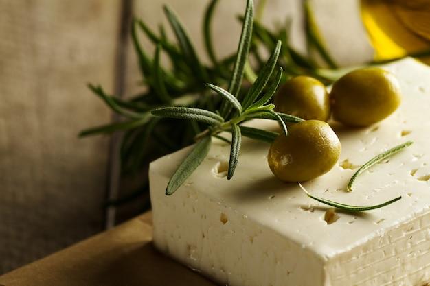 チーズフェタまたはヤギチーズの新鮮なおいしいギリシャ緑のオリーブ。閉じる。地中海料理。横。