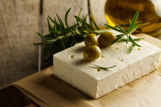 チーズフェタまたはヤギチーズの新鮮なおいしいギリシャ緑のオリーブ。閉じる。地中海料理。