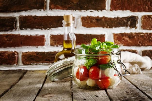 モッツァレラトマトのイタリアンフレッシュなおいしいサラダオリーブオイルと焼きたての木製テーブルのフレッシュバジル。水平。