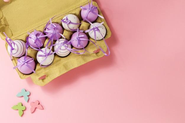 イースターまたは春、食品コンセプト。ピンクのパステルの背景に卵のためのボックスの新鮮な卵。上面図。