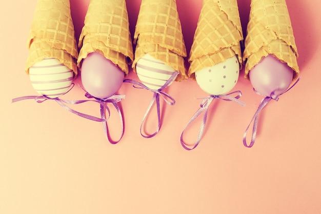ピンクの背景にイースターエッグとカラフルなアイスクリームコーン。バニラまたはパステル調子。ミニマリズムフラットレイ。