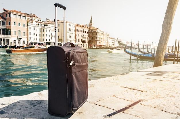 Маленький чемодан на фоне городских поездок, венеция, италия. горизонтальный. тонизирующий. концепция туристического отпуска.