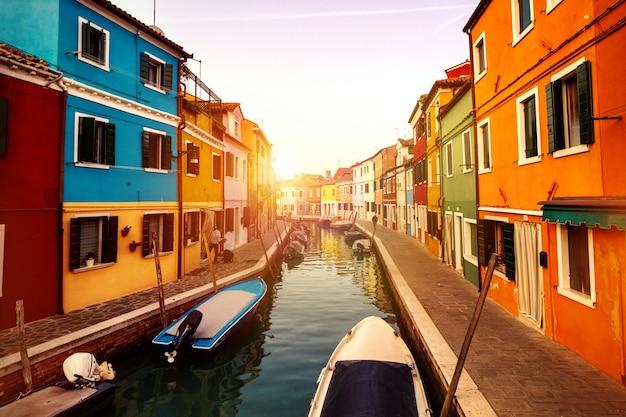 Красивый закат с лодками, зданиями и водой. солнечный лучик. тонизирующий. бурано, италия.