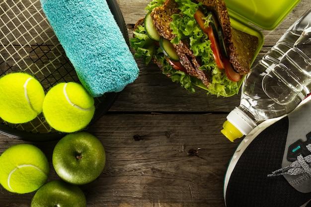 健康的なスポーツスポーツの概念。テニスボール、タオル、リンゴ、健康サンドイッチ、木製の背景に水のボトルを持つスニーカー。スペースをコピーします。上。