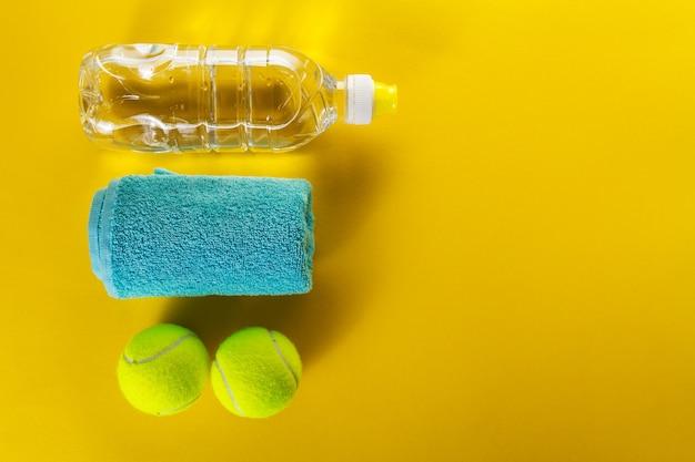 健康的なスポーツスポーツの概念。テニスボール、タオル、明るい黄色の背景に水のボトル。スペースをコピーします。フラットレイ。
