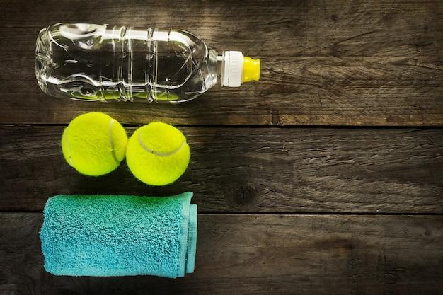 健康的なスポーツスポーツの概念。テニスボール、タオル、木の背景に水のボトル。スペースをコピーします。上面図。