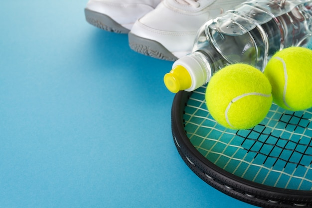 健康的なスポーツスポーツの概念。テニスボール、タオル、明るい青の背景に水のボトルスニーカー。スペースをコピーします。
