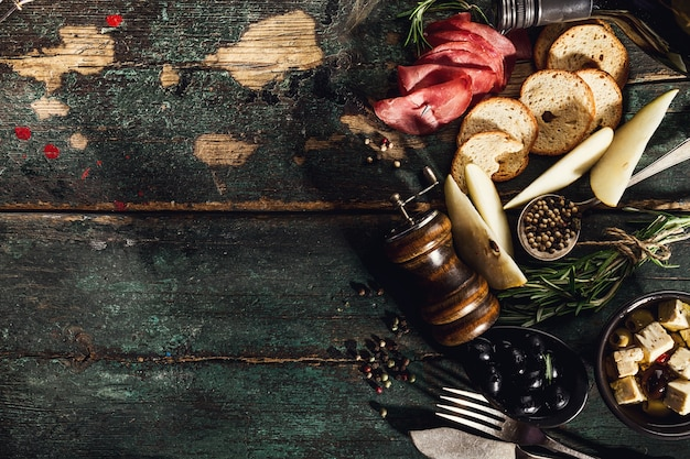 Вкусные итальянские греческие ингредиенты средиземноморской кухни вид сверху на зеленый старинный деревенский стол выше