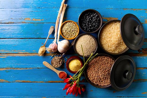 健康的なキッチンを調理するための美味しい食欲をそそる原材料スパイスの食料品。青い古い木の背景のトップビュー。