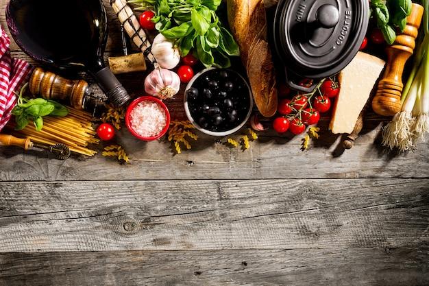 古いソーレッド木製の背景においしい食欲をそそるイタリア料理の成分。調理する準備ができました。ホームイタリアの健康食品調理の概念。